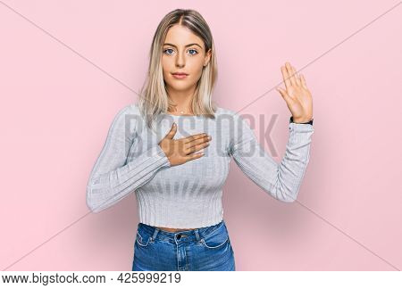 Beautiful blonde woman wearing casual clothes swearing with hand on chest and open palm, making a loyalty promise oath