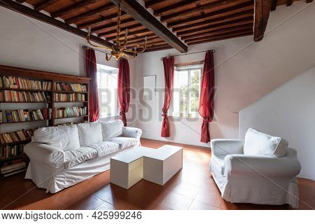 Large living room with white armchairs and sofas. A bit decadent environment. No people inside.