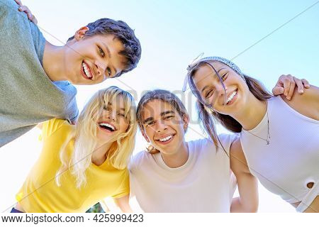 Close-up Of Happy Smiling Teenage Faces. Hugging Teenagers Looking At The Camera, Sky Background.