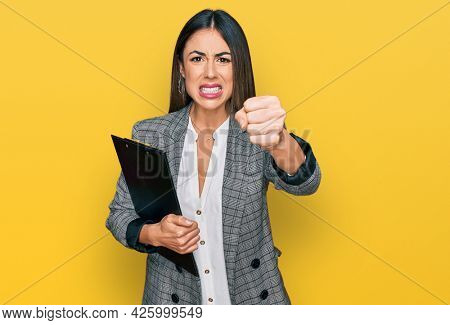 Young hispanic woman wearing business clothes holding clipboard annoyed and frustrated shouting with anger, yelling crazy with anger and hand raised