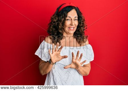 Middle age hispanic woman wearing casual clothes disgusted expression, displeased and fearful doing disgust face because aversion reaction. with hands raised