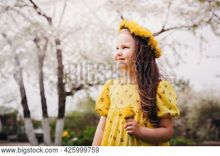 Close-up Portrait In Profile Of A Smiling Girl In A Yellow Dress And A Wreath Of Yellow Dandelions O