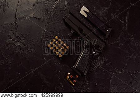 Flat Lay Of Cartridges And Gun On Concrete Background. Pistol And Bullets On Black Table. Weapons Of