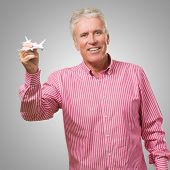 Happy Mature Man Holding Miniature Airplane against a grey background poster