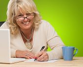 Happy Mature Woman Writing On Paper against a green background poster
