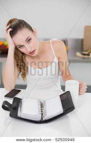 Stressed young woman holding a mug with open diary in the kitchen at home
