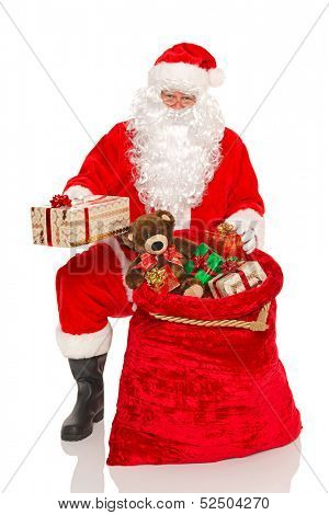 Santa Claus or Father Christmas handing out gifts from his sack, isolated on a white background.