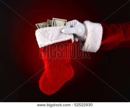 Closeup of Santa Claus holding a stocking full of cash.