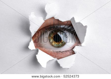 Womans eye peeking through a hole in white paper