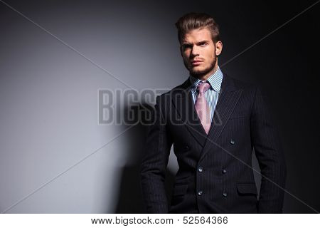 young fashion business man standing with his hands in his pockets and looking away on gray background