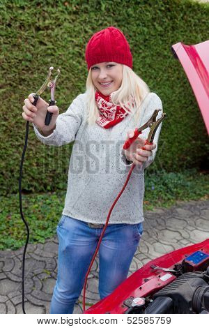 a young woman takes off her car with jumper cables. jump start on cold days in winter