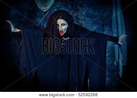 Bloodthirsty vampire flying at the night cemetery in the mist and moonlight.
