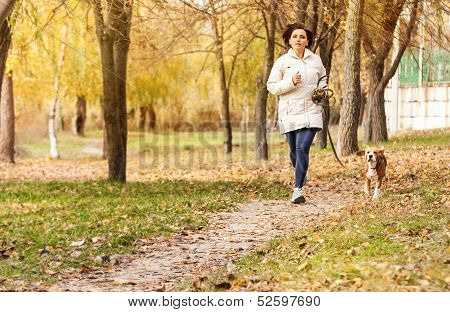 Young woman jogging with her pet in autumn park poster