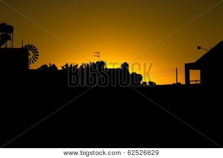 Silhouette Of Houses With A Church. Sunset