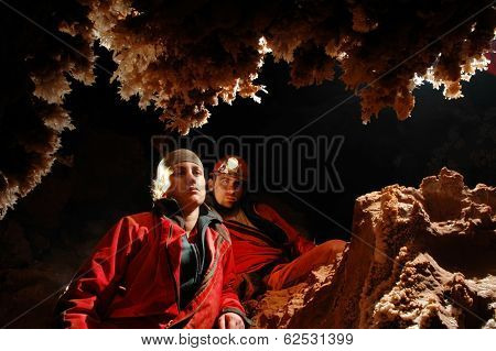 Spelunkers Admiring Stalactites In A Cave