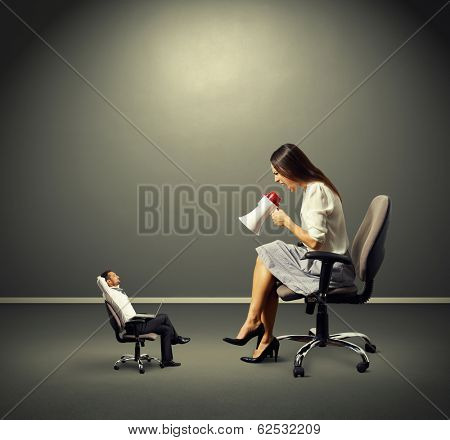 smiley small man listening angry big woman over dark background