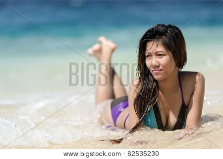 Filipina woman lying on the seashore in a sunny day
