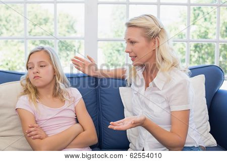 Mother scolding daughter while sitting on sofa at home