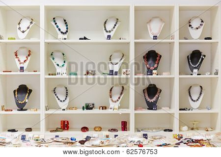 Presentation of retail showcase in jewelry store with necklaces and other jewelry