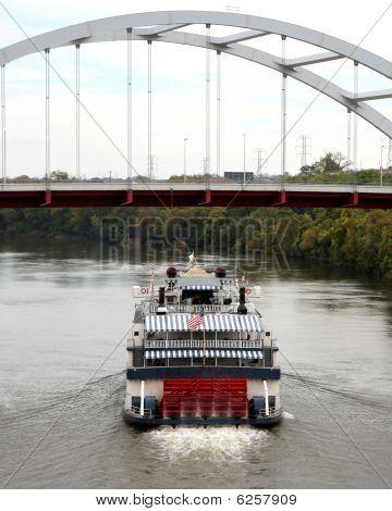 Paddleboat Sailing Under A Suspension Bridge