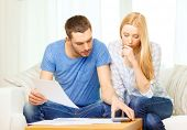 tax, finances, family, home and happiness concept - busy couple with papers and calculator at home poster