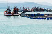 Cage aquaculture farming is done on coastline and nice fishing boat prepares before a fishingThailand. poster
