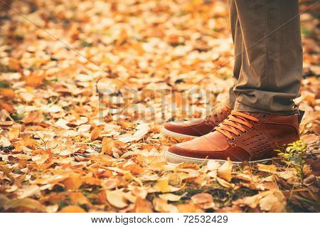 Feet Man walking on fall leaves Outdoor