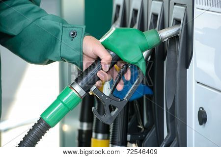 Close-up of a men's hand using a fuel nozzle at a gas station. Petrol station. Filling station. Petrol. Gasoline. poster