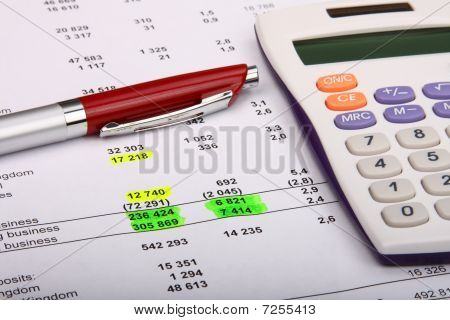 White Calculator And A Red Pen On A Financial Report
