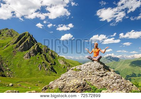 Young woman sitting in yoga pose in mountains