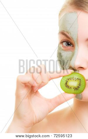 Skin care. Woman in clay mud mask on face covering mouth with slice of kiwi isolated. Girl taking care of dry complexion. poster