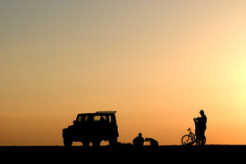 Silhouette Of People, Cars And Bicycle At Sunset