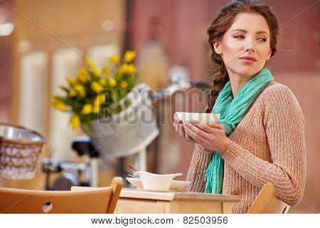 beautiful young girl drinking coffee in a old town cafe - outdoor portrait