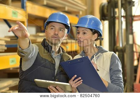 Worker with overseer controling stock in warehouse