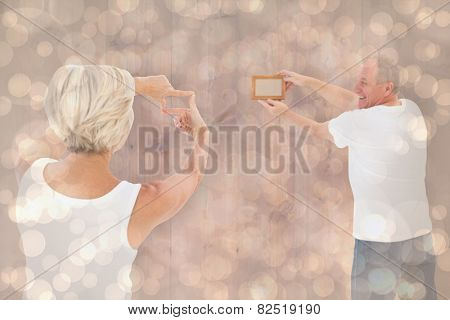 Mature couple hanging up picture frame against light glowing dots design pattern