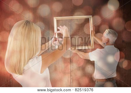 Couple hanging a frame together against light circles on black background