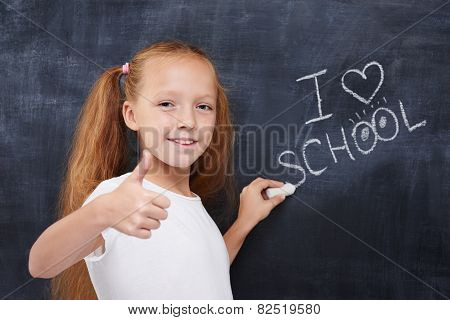 Cute redhead schoolgirl showing thumbs up and smile