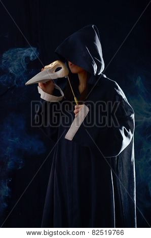 the girl in monastic robes holding a medieval mask.on a dark background with smoke