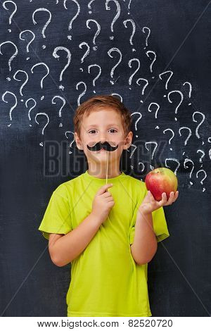 Portrait of cheerful ginger boy with fake moustache and apple