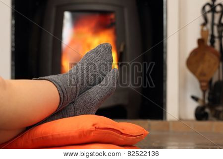 Woman feet with socks resting near fire place with a warmth background poster