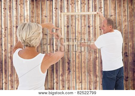 Mature couple hanging up picture frame against wooden planks