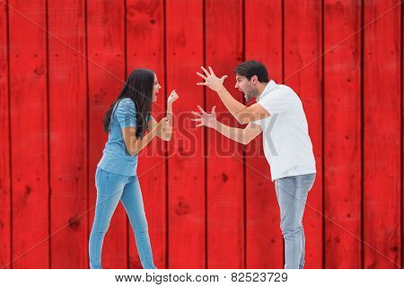 Angry couple shouting at each other against red wooden planks