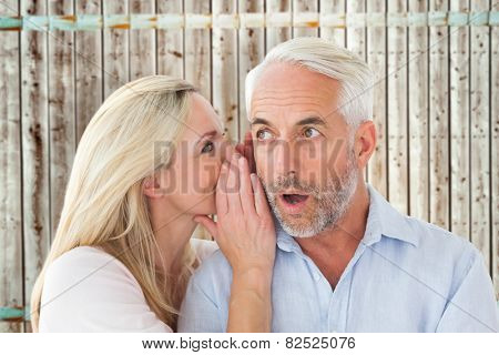 Woman whispering a secret to husband against wooden background in pale wood