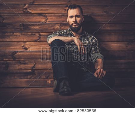 Handsome man wearing checkered  shirt in wooden rural house interior