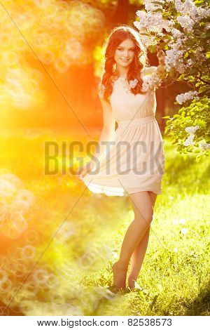 Young spring fashion woman  in spring garden. Springtime. Trendy girl at sunset in spring landscape background. Allergic to pollen of flowers. Spring allergy poster