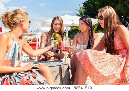 Four woman sitting in beach bar, drinking fancy cocktails and tanning in the sun