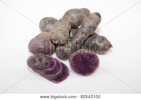 Sliced and whole purple Vitelotte potatoes. Isolated over white background poster