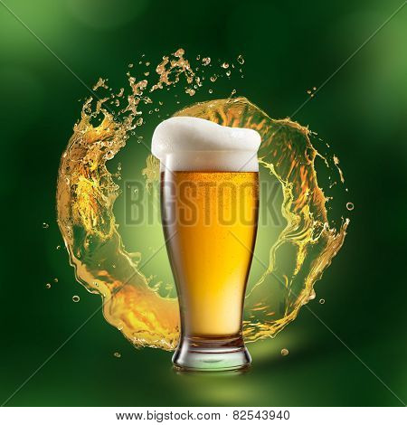 Beer in glass with splash on green natural background