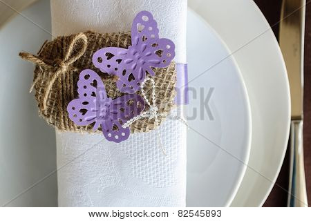 napkin decorated with two violet butterflies and twine tied in a bow
