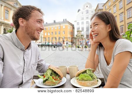 Couple eating food at Cafe in Stockholm, Sweden, Europe. Happy multiracial young couple outside on Stortorget big square in Gamla Stan, the old town of Stockholm. Scandinavian man, Asian woman.